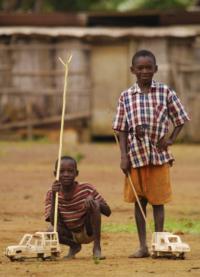 Bambini che giocano con due macchinine di legno nel villaggio